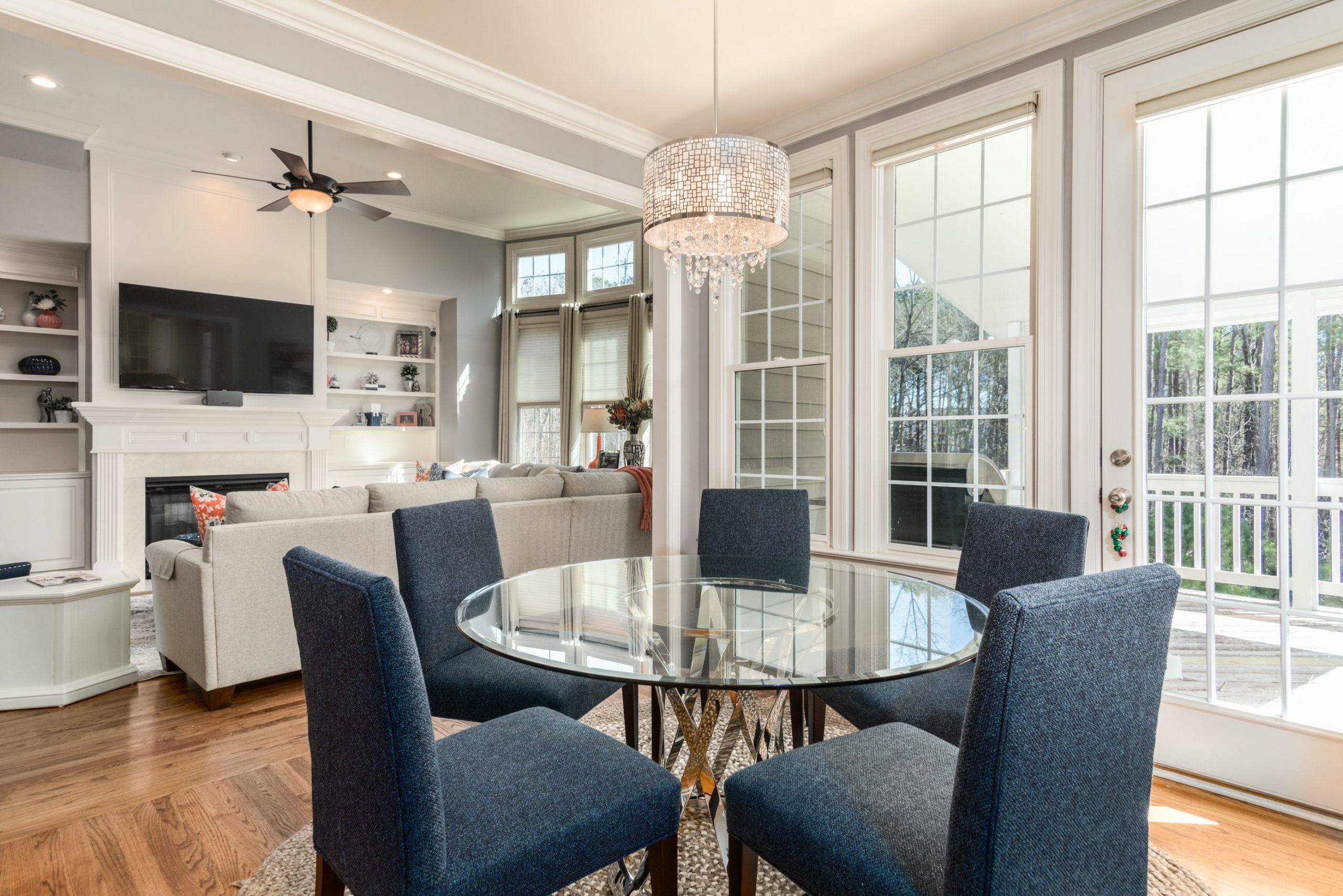 round clear glass-top table and five gray chairs dining